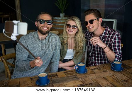 Happy friends taking selfie with monopod at table in coffee shop