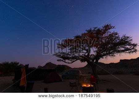 Camping site with starry sky by night. Adventure in National Park Africa. Burning camp fire and tent with big acacia tree.
