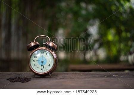 Alarm clock with coffee beans on wooden table with morning light Start up concept