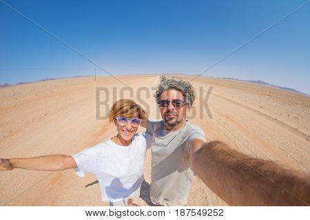 Adult Couple Taking Selfie On Gravel Road In The Namib Desert, Namib Naukluft National Park, Main Tr
