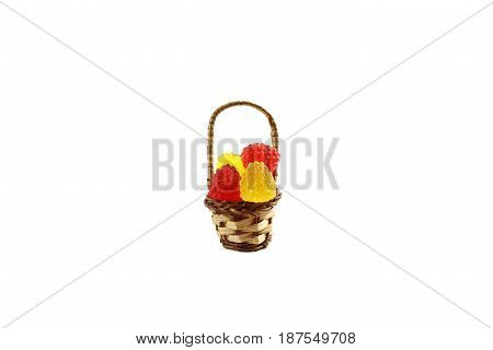 Candy of marmalade in the form of raspberries, in a wicker basket on a white background