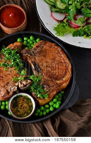Steak grilled with a garnish of green peas and tomato sauce