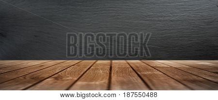 Rustic wooden table in front of a wall from slate for a decoration