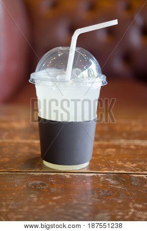 Ice lemonade in takeaway cup on wooden table