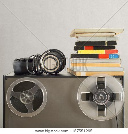 Vintage magnetic audio reels and headphones on the analog tape recorder near the stucco wall