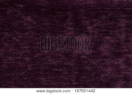 Dark purple background of soft fleecy cloth. Texture of light maroon nappy textile closeup.