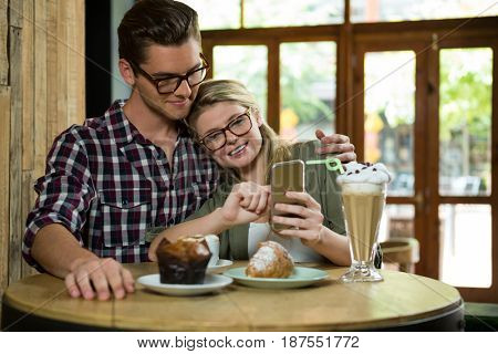 Loving young couple using smart phone at table in coffee shop