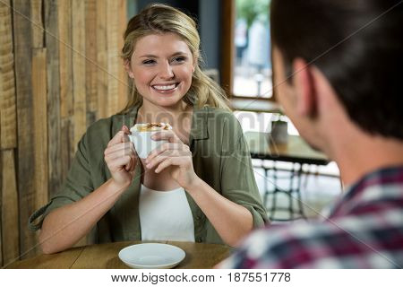 Smiling young woman holding coffee cup while looking at man in cafe
