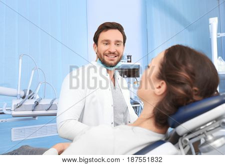 Male dentist with patient in clinic