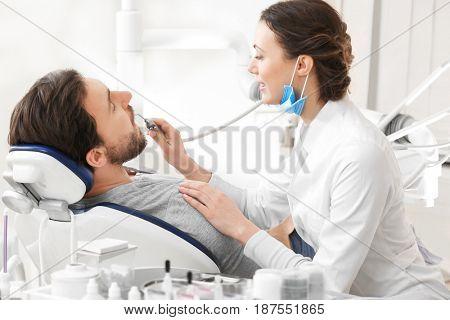 Dentist examining patient's teeth in clinic
