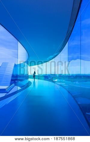 Aarhus, Denmark - May 2, 2017: A young woman walks through the blue tinted area of an installation by Danish-Icelandic artist Olafur Eliasson on rooftop of ARoS art museum.