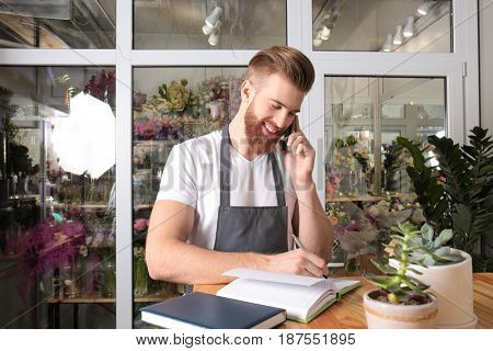 Young handsome florist writing order while talking by mobile phone in flower shop