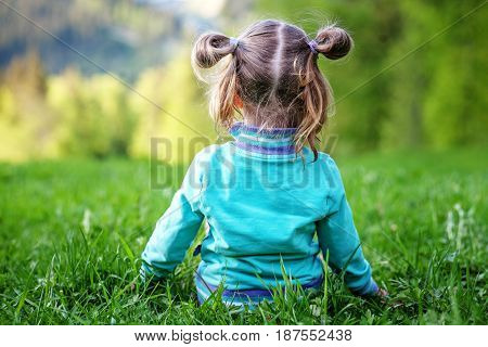 Little kid sitting on the grass. Summer. The concept of travel lifestyle and childhood.