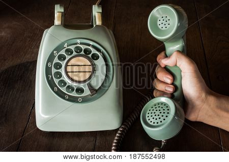 Close Up Of Hand Holding Old Black Rotary Telephone With Dust On Telephone On Wooden Retro Table. Ol
