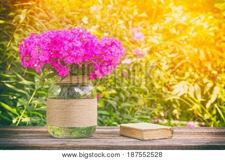 summer still life of bouquet of flowers Phlox and little old book on wooden table on natural Sunny background tinted photo