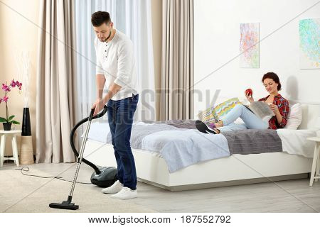 Woman reading newspaper on bed while man hoovering floor at home