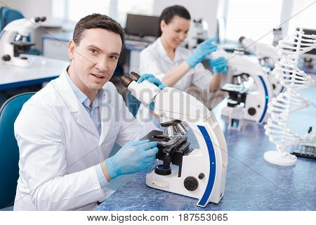 It is really interesting. Positive male person sitting in semi position and keeping mouth opened while touching microscope