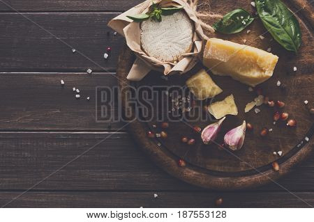 Cheese delikatessen background closeup on rustic wood. Wooden desk with parmesan, camembert and brie cuts decorated with garlic, pomegranate and basil, top view image