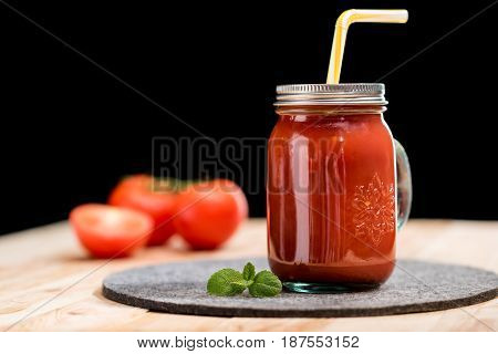 Selective Focus Of Fresh Tomato Smoothie With Basil Leaves And Straw On Tabletop