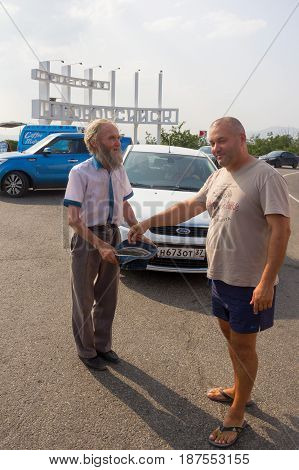 Novorossiysk Russia - July 27 2016 - Tourist gives alms to a bearded man the beg with the hat in the Parking lot at the entrance to the city
