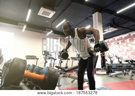 hard workout. Muscular black man wearing sportswear doing exercises with dumbbells for back at gym