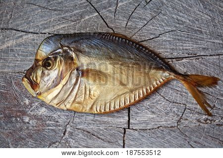 smoked fish on the wooden table, fish on wood