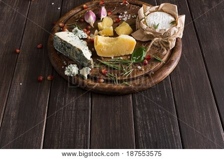 Cheese delikatessen on rustic wood, copy space. Blue cheese roquefort, parmesan, camembert and brie cuts decorated with garlic, pomegranate and basil, french cuisine ingredients