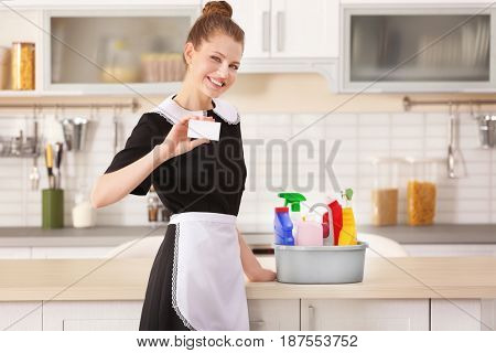 Young chambermaid with business card in kitchen
