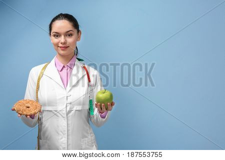 Portrait of young female nutritionist on light background