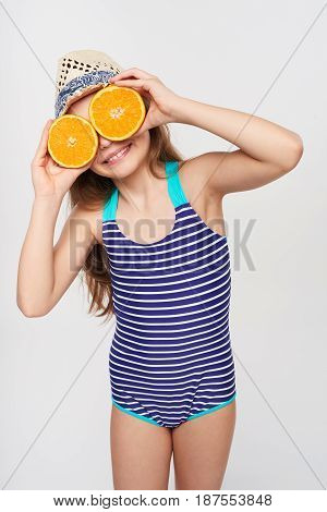 Llittle girl in swimsuit and summer hat having fun with half oranges making fake eyeglasses