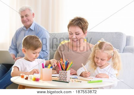 Happy senior woman painting together with grandchildren at home