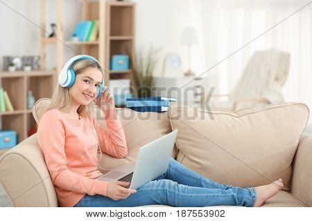 Young woman listening to audio book at home