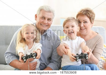 Grandparents and grandchildren playing video game together at home