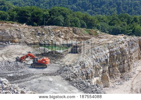 A backhoe and large truck work in the gypsum quarry in the summer. Industrial landscape