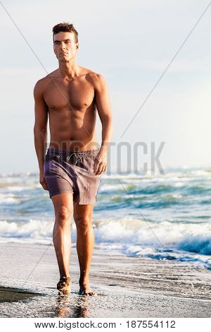 Man walking on the shore beach, sea in summer time. A charming man in shorts walking along the seashore. Waves and blue sea behind him. Lean physique and rightly muscular.