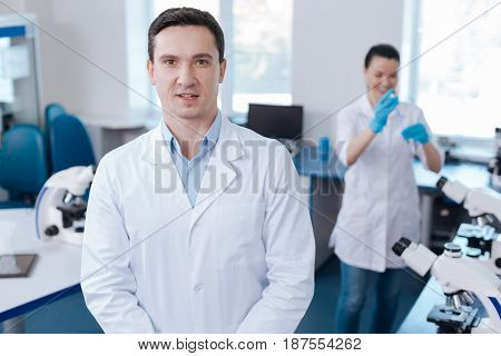 Ready for work. Handsome male person keeping his mouth opened looking straight at camera while working at the laboratory