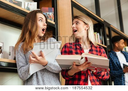 Photo of young shocked women students standing in library reading book writing notes. Looking aside.