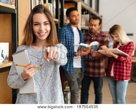Smiling young girl student holding textbook and pointing finger at camera while standing at the library with her friends on a background