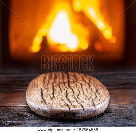 Empty chopping wooden board on the wooden table. Bright fire in the fireplace in the background.