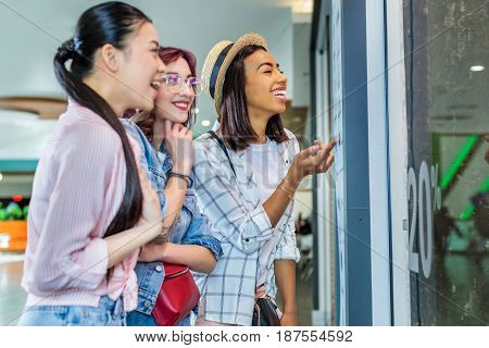 Multicultural Hipster Girls Looking At Showcase In Shopping Mall, Friends Shopping Concept