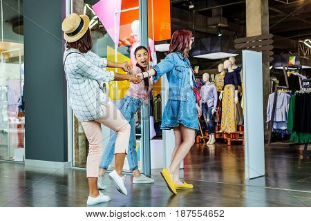 cheerful multicultural hipster girls in shopping mall friends shopping concept