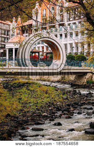 Borjomi, Samtskhe-Javakheti, Georgia - October 25, 2016: Crowne Plaza Borjomi Hotel House In Baratashvili Street And Pedestrian Bridge Over River Borjomi In Shape Of A Mobius Or Moebius Loop Or Strip