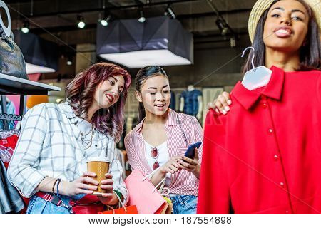 Multicultural Hipster Girls Choosing Clothes And Using Smartphone In Boutique, Fashion Shopping Girl