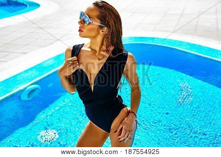 Hot Beautiful Girl Model With Dark Hair In Black Swimwear Posing Near Swimming Pool