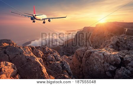 Flying airplane. Landscape with white passenger airplane rocks mountains sea and orange sky with clouds at sunset. Summer journey. Passenger airliner is landing. Business travel. Commercial plane