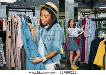 Multicultural Hipster Girls Choosing Clothes In Shopping Mall, Boutique Shopping Concept