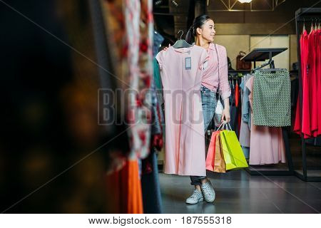 Asian Hipster Girl Holding Dress And Shopping Bags In Boutique, Clothes Shopping Concept
