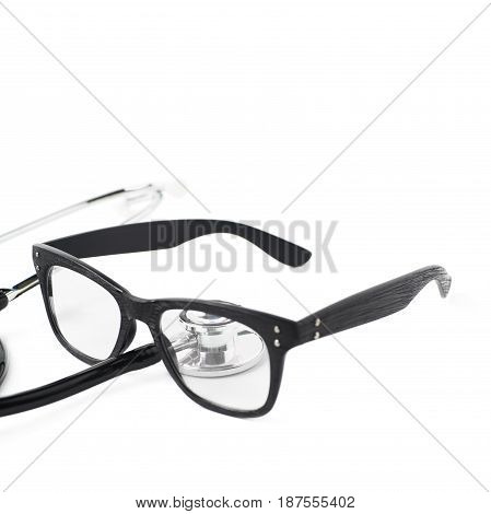Pair of wooden textured optical reading glasses next to a medical stethoscope, composition isolated over the white background, close-up crop foreshortening