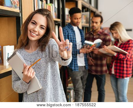 Smiling young girl student holding textbook and showing peace gesture while standing at the library with her friends on a background