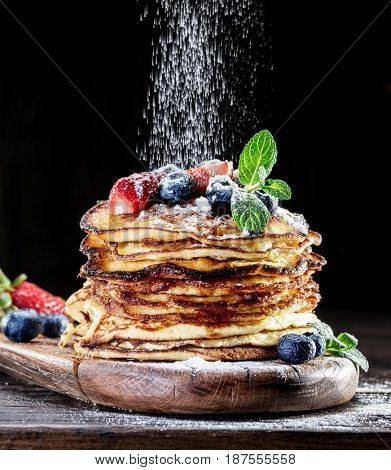 Pancakes with fresh berries on the wooden table.